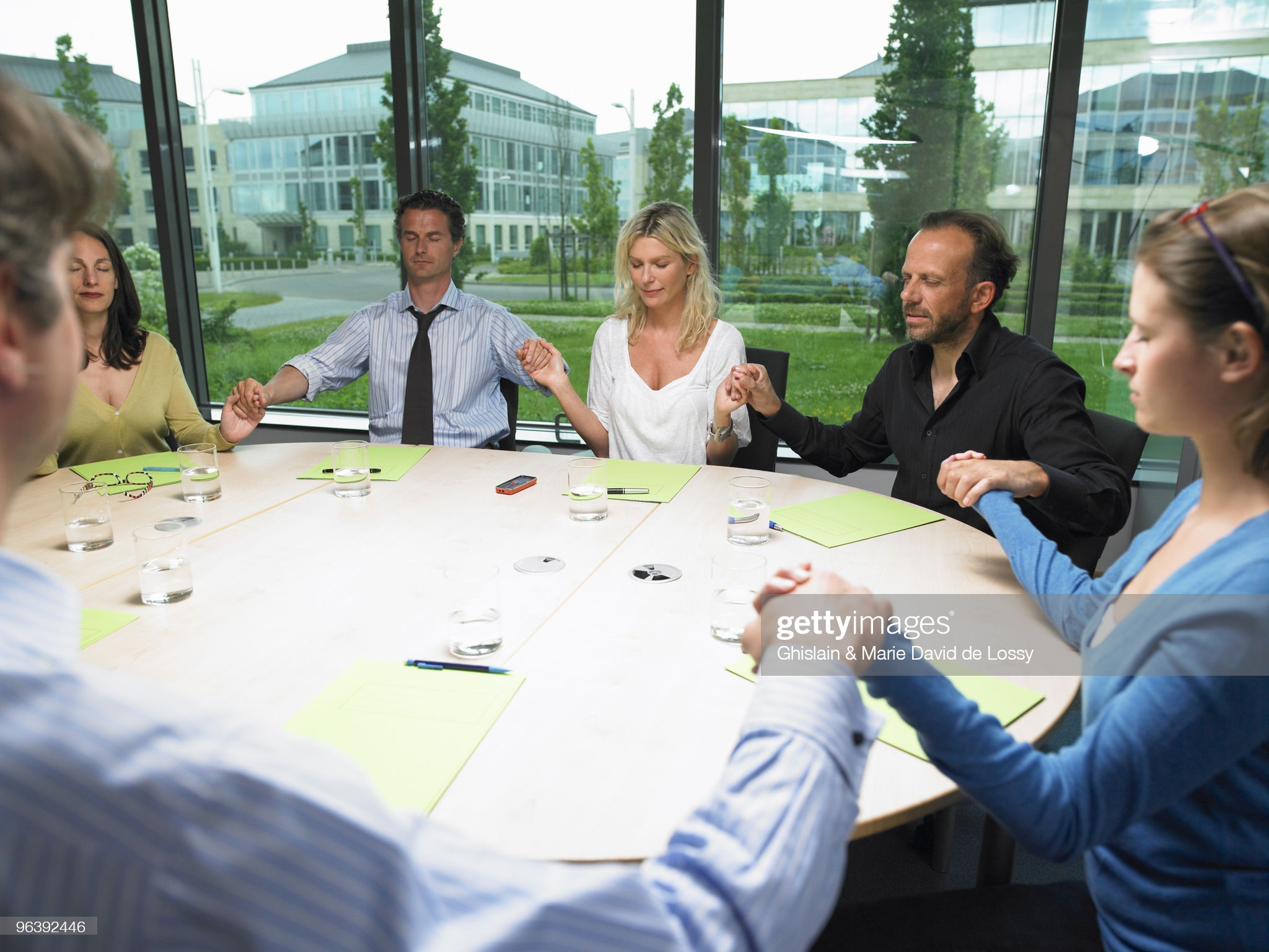 Coworkers holding hands - stock photo. Getty Images, Ghislain & Marie David de Lossy.